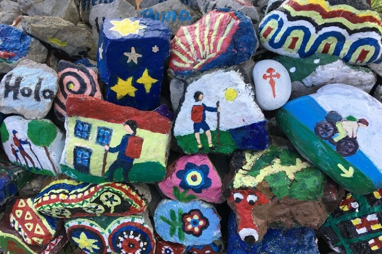 Colourful painted stones with pilgrims and hikers on them