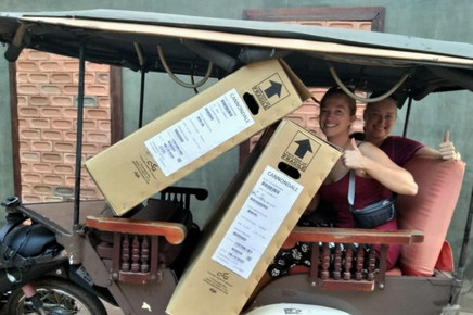 Becky and Liz are sat in a rickshaw-type vehicle. The have two big card boxes on top on them and they have thier thimbs up as they smile at the camera.