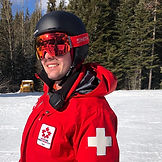 Chris Winwood wears a warm red First Responder jacker, a crash helmet and ski googles.