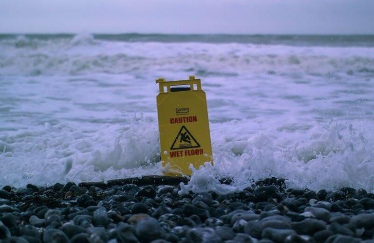 warning sign in the sea surf symbolising danger - oscar-sutton via unsplash