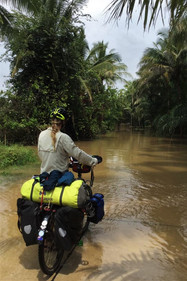 Shot from behind Becky as she stands holding her bike looking at a flooded path in the jungle.