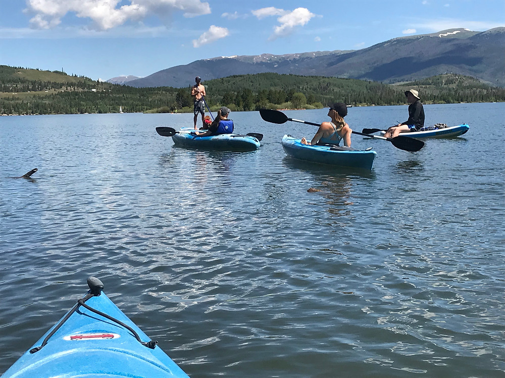 From a kayak, the pictures shows 4 Outdoor Mindset members in kayaks and one paddleboards on the lake.