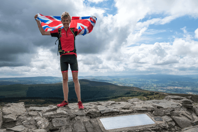 Alex standing on top of a mountain at the end of Climb the UK, holding a Union Jack flag up via Alex Staniforth