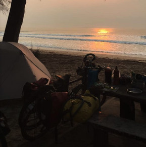 There is a tent on a beach. Becky's bike leans against a picnic bench with water bottles and food on. The sun is setting over the sea.