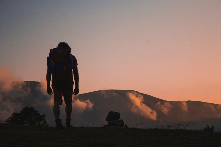 Backpacker on mountain in front of sunset - Aneta Ivanova via unsplash