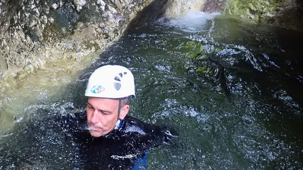 Ian is in water, surrounded by rock. He wears a helmet and is spitting out water.