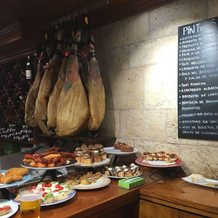 Sorreno ham legs hanging in bar with pinxos