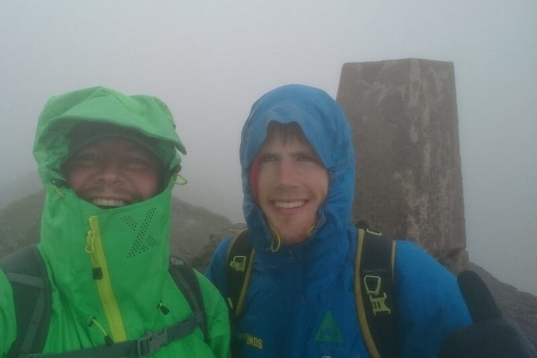 Alex and Friend in rain gear in the fog, with a mountain trig point behind them