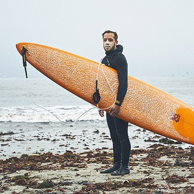 Full length shot of a man in black wetsuit standing on a seaweed-covered beach, holding an orange surfboard and looking directly at the camera.