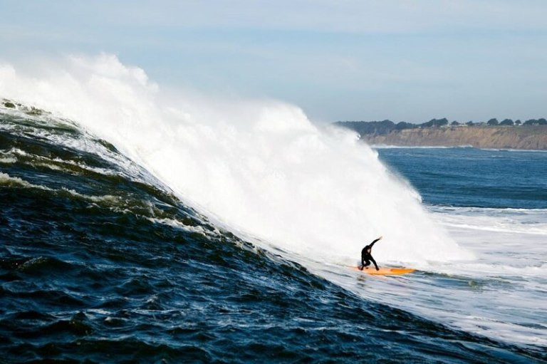 Man on yellow surfboard on Mavericks wave by Billy Watts