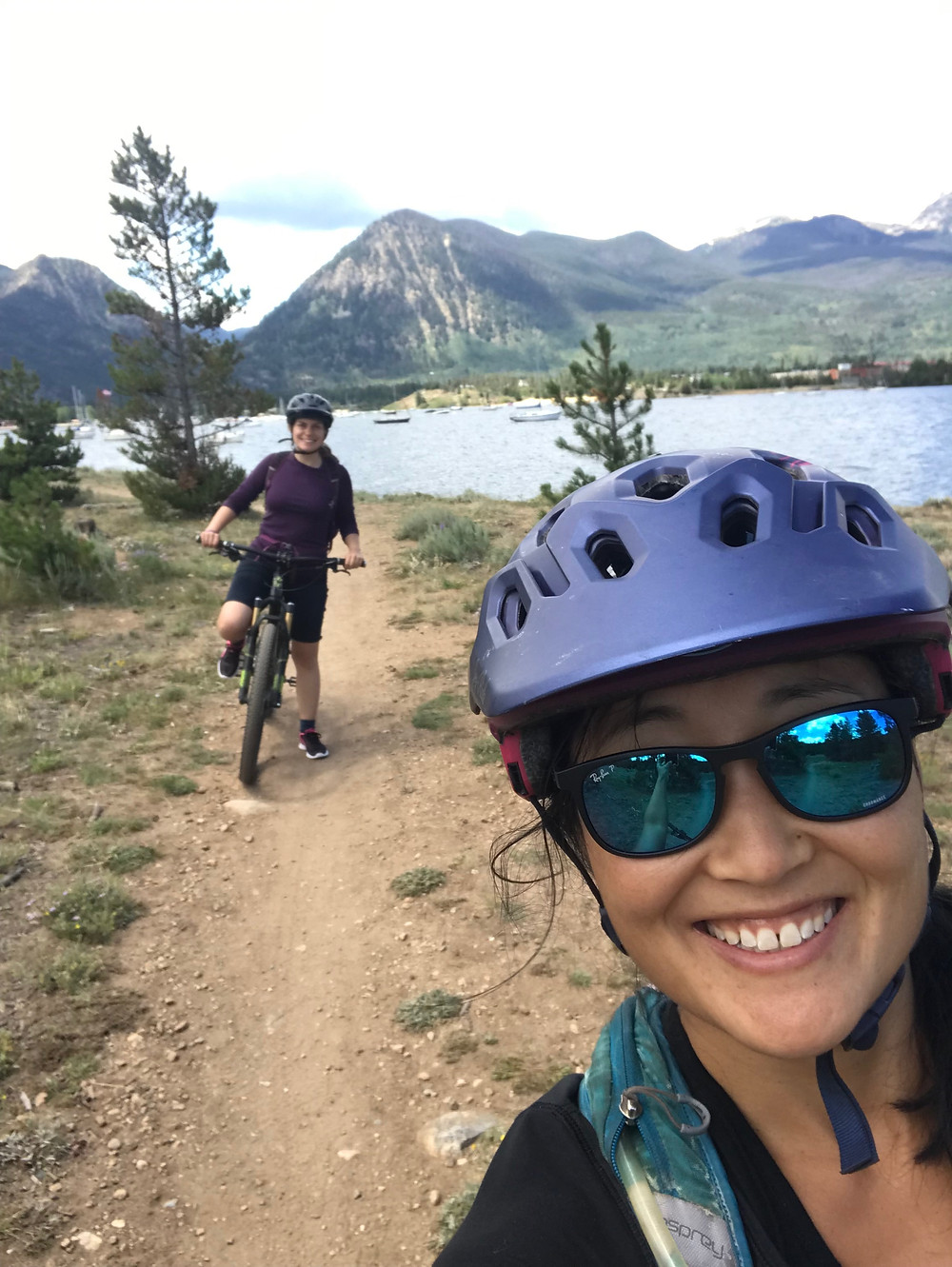 Jeanie takes a selfie in a bike helmet and sunglasses. Fran is behind on her bike. There are mountains in the background.
