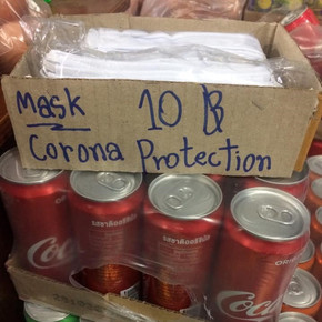 A box of facemasks sit on top of a pack of coca-cola cans. The box reads 'Mask 10 Corona Protection'