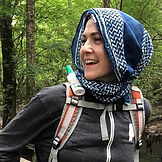 Jade Nelson wearing a day pack and head scarf, laughing