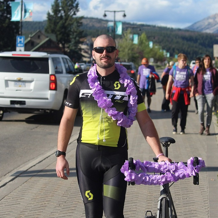 Photo by Taylor McElderry. Chris walks his bike at the end of the ride. He is wearing his jersey and purple flower lei.