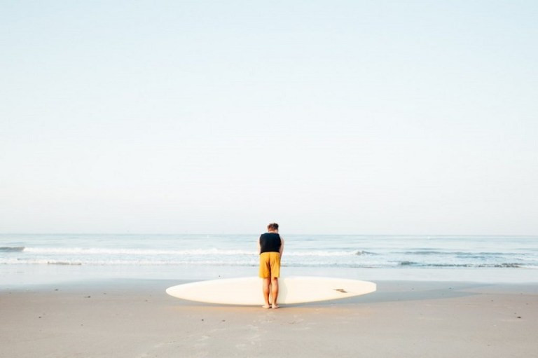 Man in yellow boardshorts facing a calm ocean, his paddlebard horizontal at his feet  by Nick Liotta