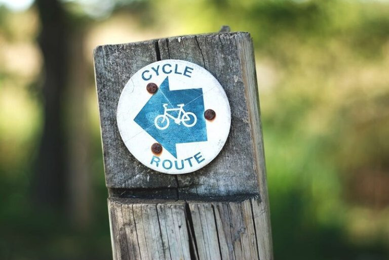 cycle route on wooden sign post - gemma-evans via unsplash