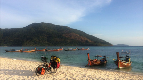 Becky's bike on a beach in Thailand. Local boats in the water and a tree-covered hill in the background.