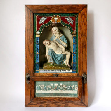 plaster pieta behind glass with a wood frame