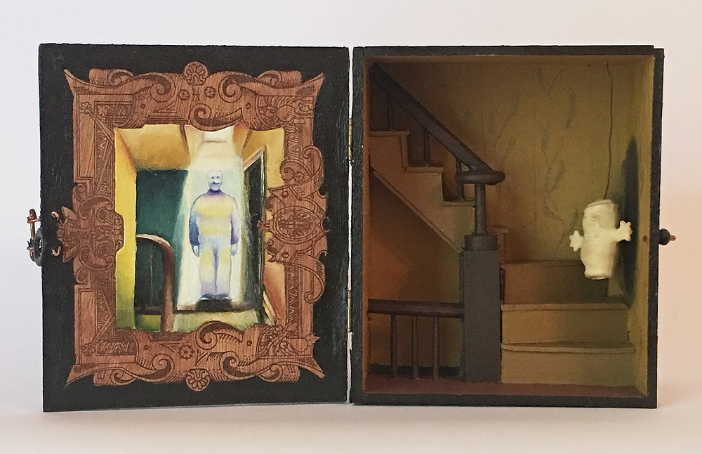 Interior of box with oil painting on left side and model of staircase on left side.