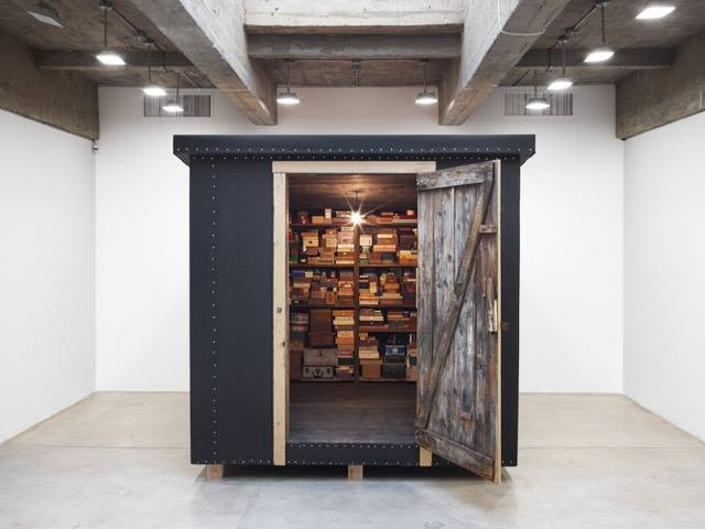 Shed like structure in an art gallery. The door is open showing many small boxes stacked on shelves.