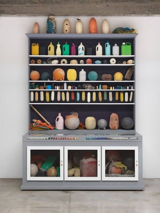 Shelves and cabinet with plastic bottles and other colored plastic items.