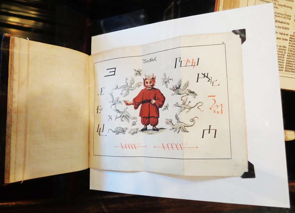 Book opened to a fold out page. Page has an image of a demon dressed in red printed on it.
