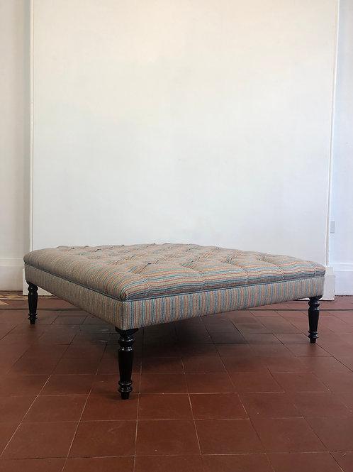 A handmade deep buttoned upholstered footstool