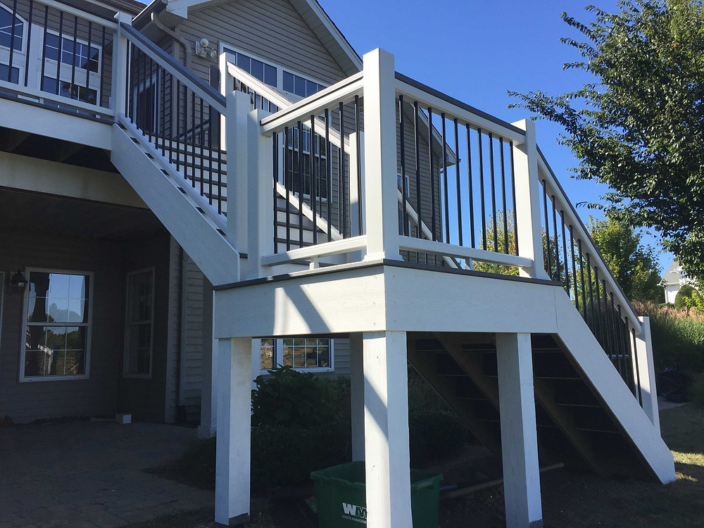 Trex Transcends deck with white fascia, black aluminum balusters, and grey handrails.