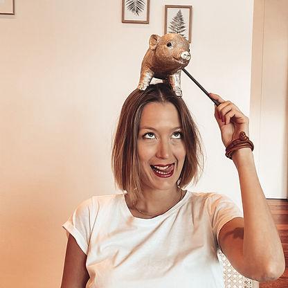 Leonie schneidet Grimassen und kitzelt ein kleines Keramikschwein das auf ihrem dem Kopf balanciert