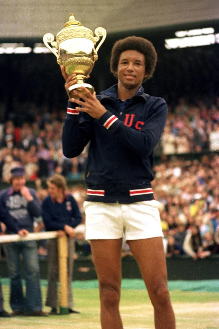 Arthur Ashe holds up the Wimbledon Championship Trophy