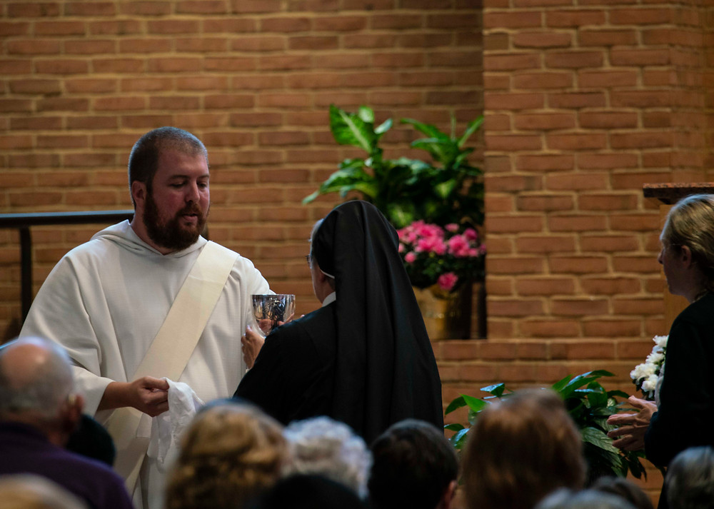 Deacon Max distributing Communion to an Augustinian sister