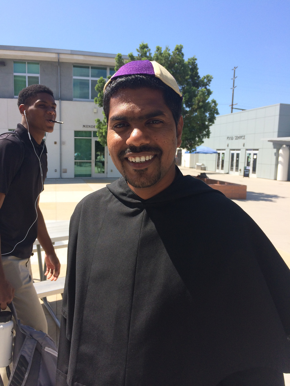 """Br. Sarfraz wearing his """"beanie"""" in front of the campus ministry office"""
