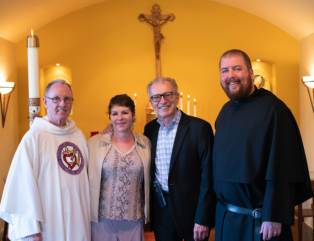 Fr. Kevin takes a picture with Br. Max and his parents after the Mass