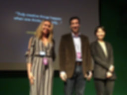 Steven Edell presenting the award to Shelby Adair and Becky Baihui Chen on stage at Blackmagic Colle