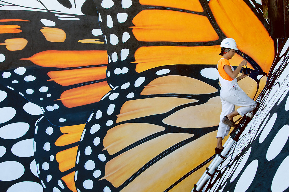 Jane Kim of Ink Dwell painting the Monarch in Moda mural