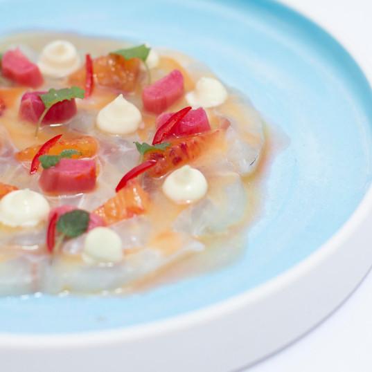 Seabass carpaccio, blood orange & chilli dressing, lime sour cream & mint