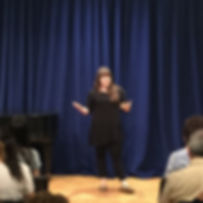 Samantha Gambaccini speaking to students and parents at a recital