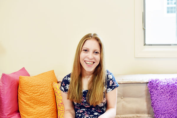 A picture of Caitlin sitting down smiling at the camera