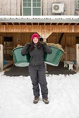 Farm girl carying hay bucket