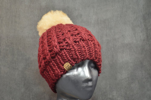 Red colored tuque with pompom hand knitted with alpaca yarn