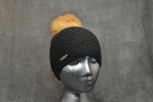 Black colored hat with pompom hand knit with alpaca yarn