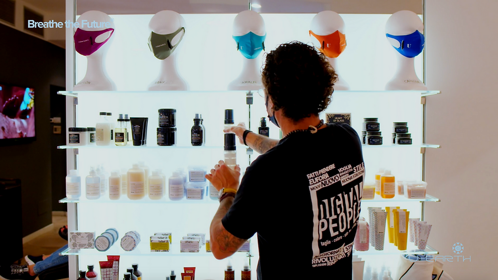 A man stands in front of custom U-Masks and hair products at Rubertelli Hair salon in Milan.