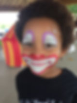 girl paintd as clown smiles big