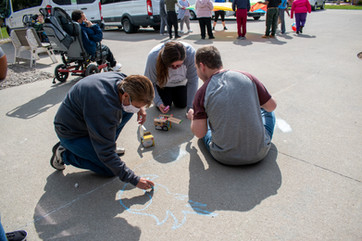 man with a disability drawing with chalk