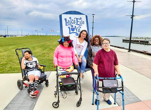 """4 women and one man posing in front of the """"lake erie love"""" giant blue chair."""
