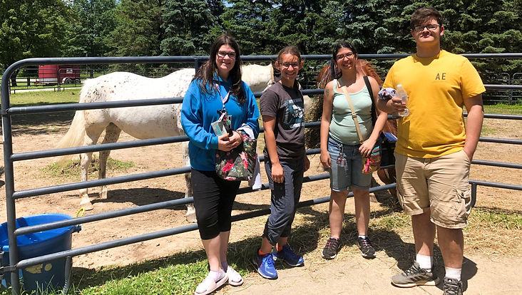 3 teenage women and one teen man standing in front of horses
