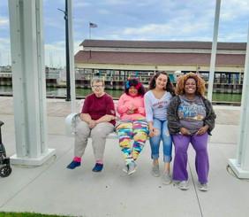 4 women sitting on a large swing chair.jpg