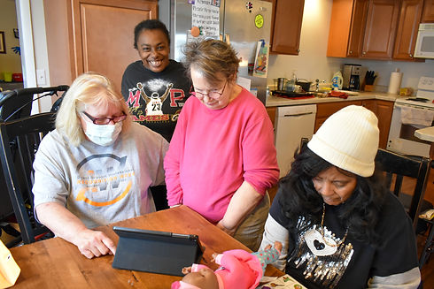 4 women at a table looking down at a tablet