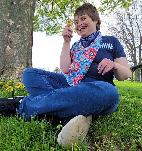 woman sitting under a tree smiling at a dandelion she is holding