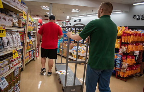 two men pushing a loading cart through the grocery store